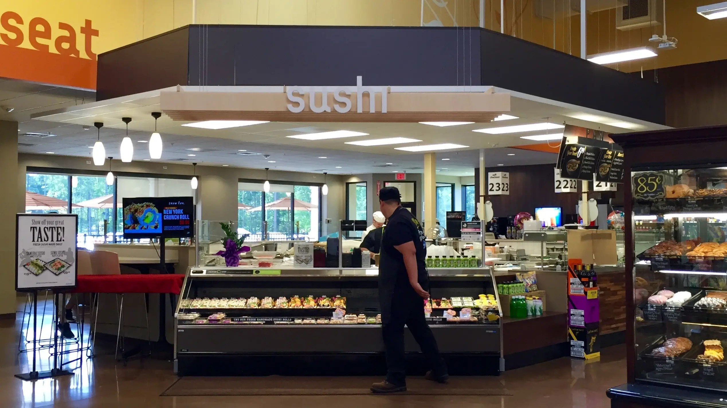 Just beyond the produce department, there are several prepared-food counters like this one, where three chefs are behind the counter rolling sushi.