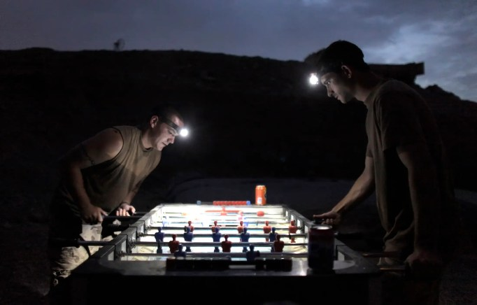 NATO soldiers play table soccer under flashlights at a military outpost near the village of Bazaar e Panjwaii, in the Panjwaii district of Kandahar province, August 2010.