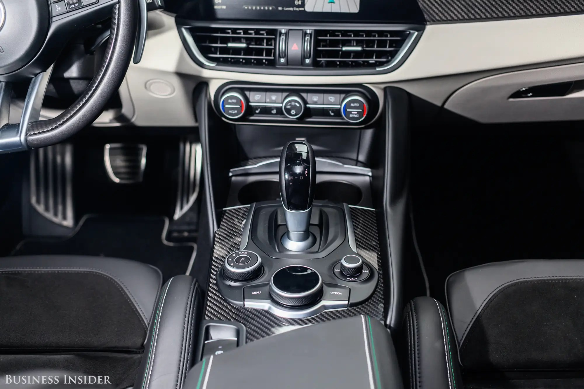 The central console presents a drive-mode selector — Dynamic, Natural, Advanced Efficiency, and Race are on tap — and a hockey-puck-style infotainment knob, all framed in carbon fiber.