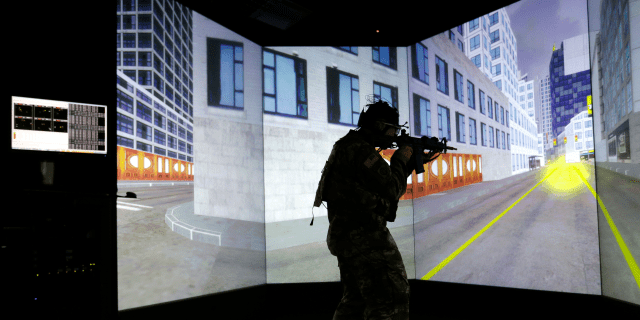 A soldier stands in a virtual reality lab wearing a headset to measure his cognitive responses under stress