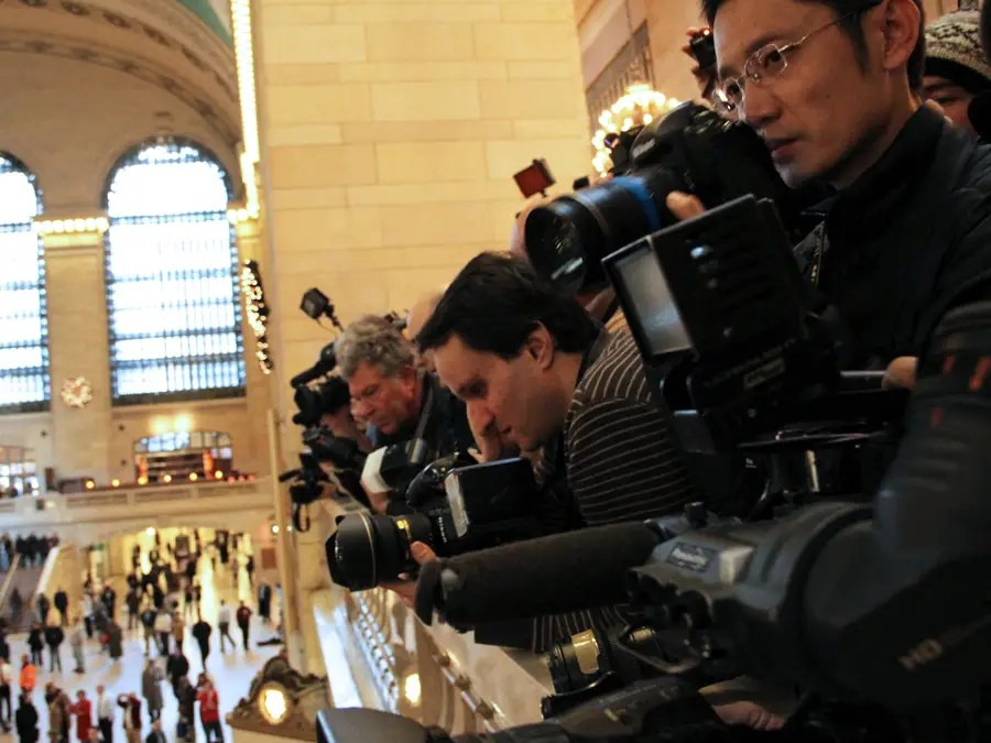 A mob of photographers lined the railing, snapping up shots of the controlled chaos