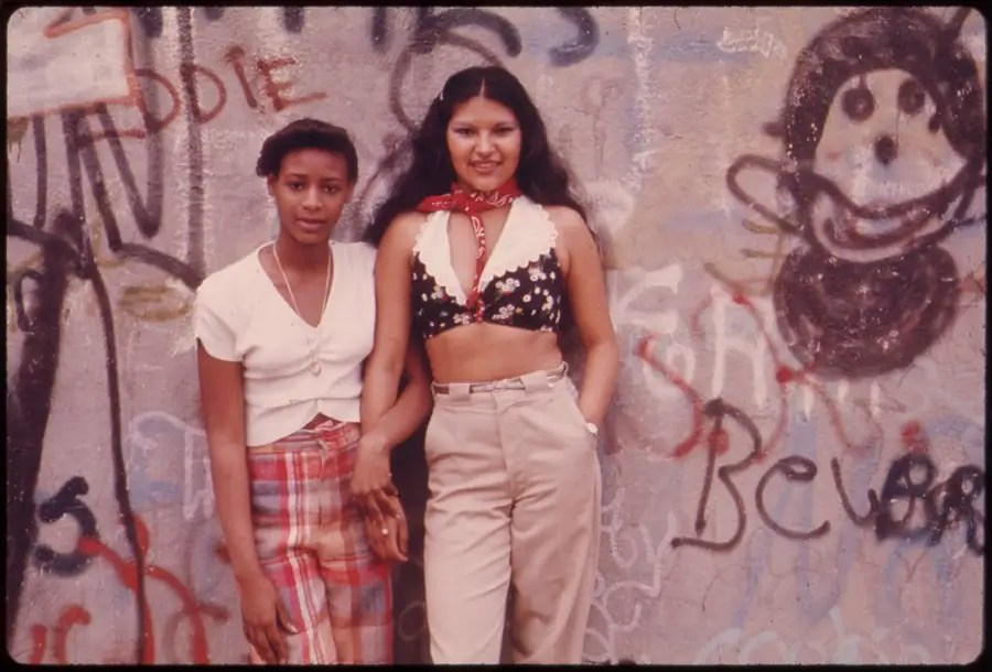 Two Latino girls pose in front of graffiti in Lynch Park, Brooklyn