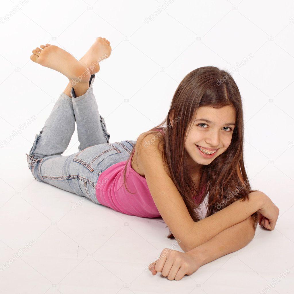 Attractive Teenage Girl Lying On Floor Isolated On White