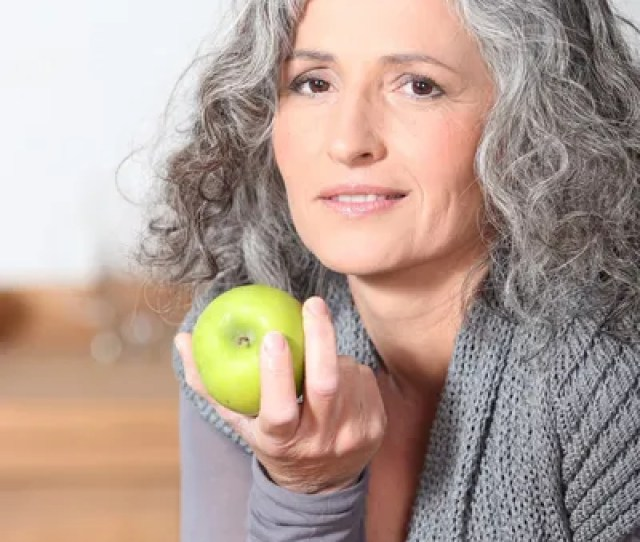 Beautiful Mature Woman Eating Green Apple Stock Photo