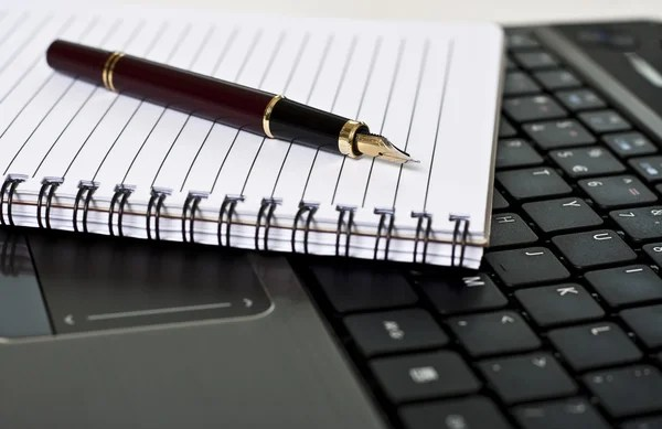 Pen, notepad and laptop on the desk stock image