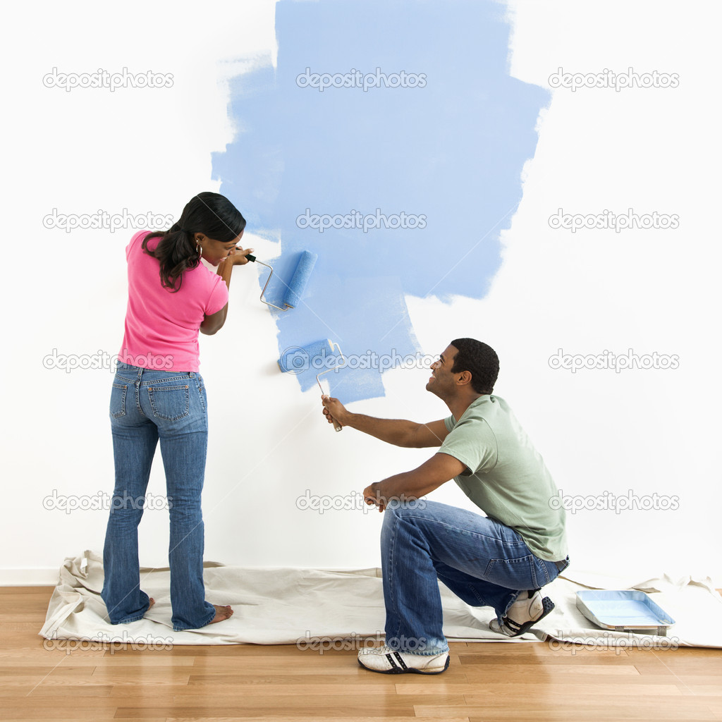 Couple painting wall blue.  Stock Photo  iofoto #9312376