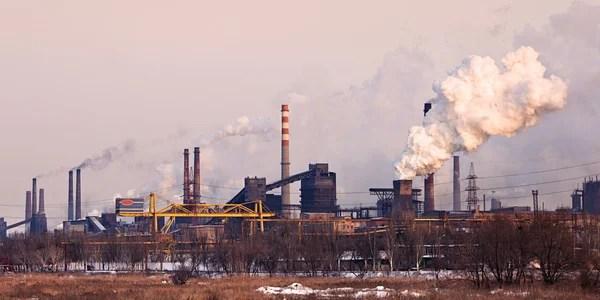 Paesaggio industriale con camino di fabbrica e fumo  Foto