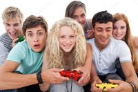 Excited teenagers playing video games in the living-room ...