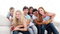 Adolescentes jugando juegos de video en la sala de estar ...
