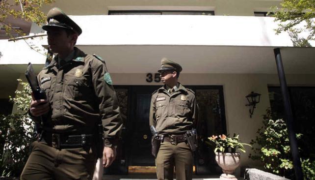 Guardia. Policías chilenos custodiaban ayer la residencia de Mena luego de constatarse su suicidio (AP).