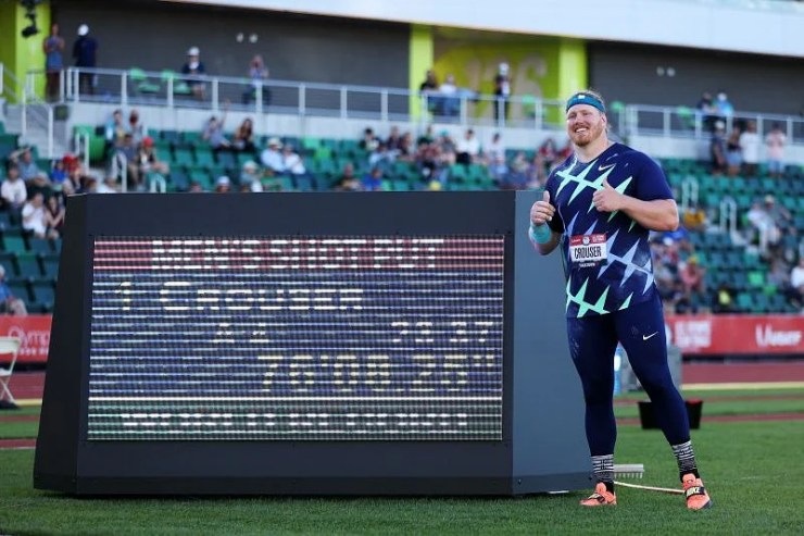 Ryan Crouser alongside the display board flashing his WR in shot put at US Olympic Track and Field Trials 2021