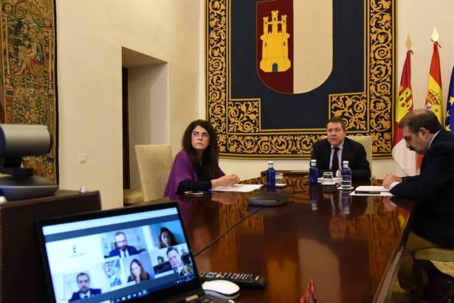 El presidente de Castilla-La Mancha, Emiliano García Page; el consejero de Sanidad, Jesús Fernández, y la directora general de Ordenación Farmacéutica, Carmen Encinas en videoconferencia con los cinco presidentes de los COF de la comunidad.