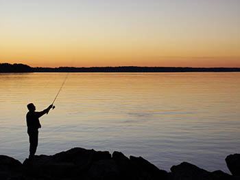 Image of a person fishing at sunset.