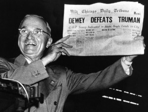 Photograph of Truman holding newspaper.
