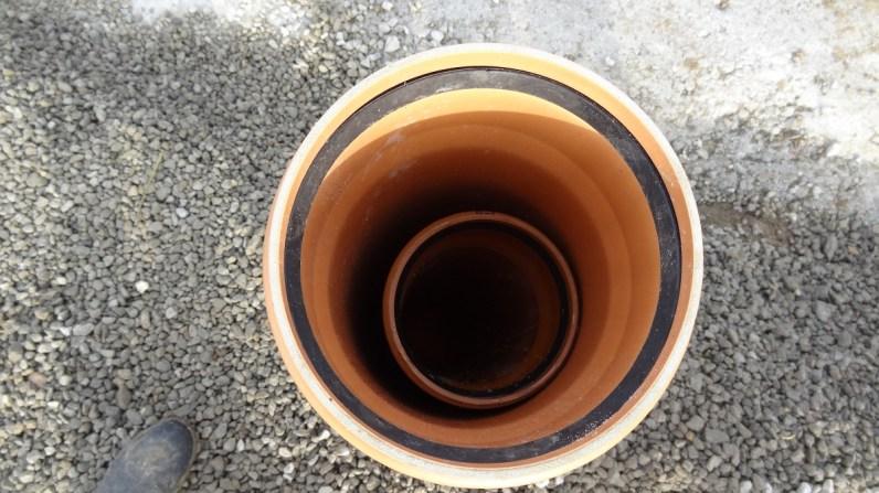 Vývod kanalizačního potrubí překrytý širší trubkou