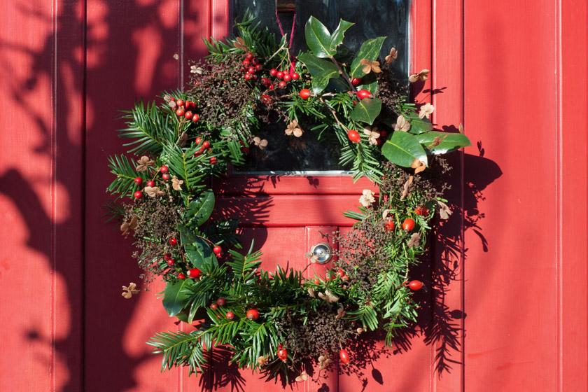 Green wreath hanging on red door