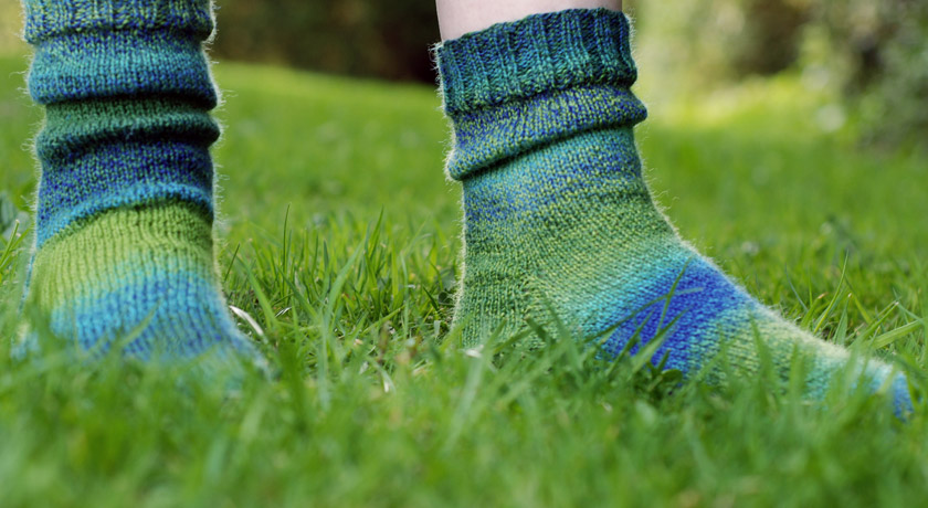 Side view of green and blue knitted socks on grass
