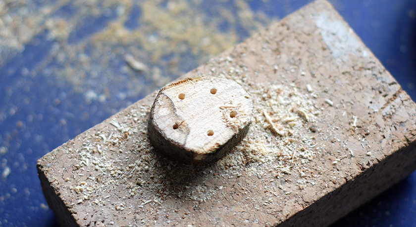 Wooden disc with 5 drilled holes
