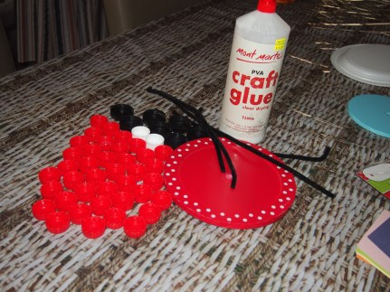 Bottle caps of your choice, craft glue, a round piece of card board or plastic, pipe cleaners and goggly eyes