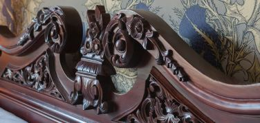 Ornate carved headboard on four poster bed with a background of thistle design wallpaper