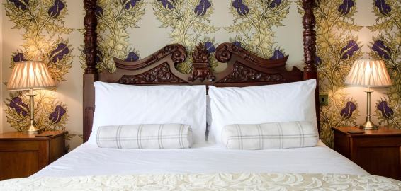 Ornate carved headboard on a four poster bed with white bedding against an intricate thistle pattern wallpaper