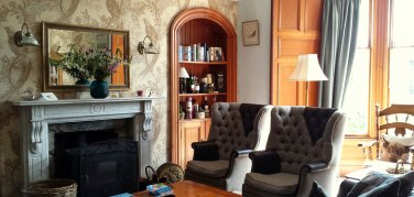 High backed chairs in the guests lounge at Strathallan Guest House
