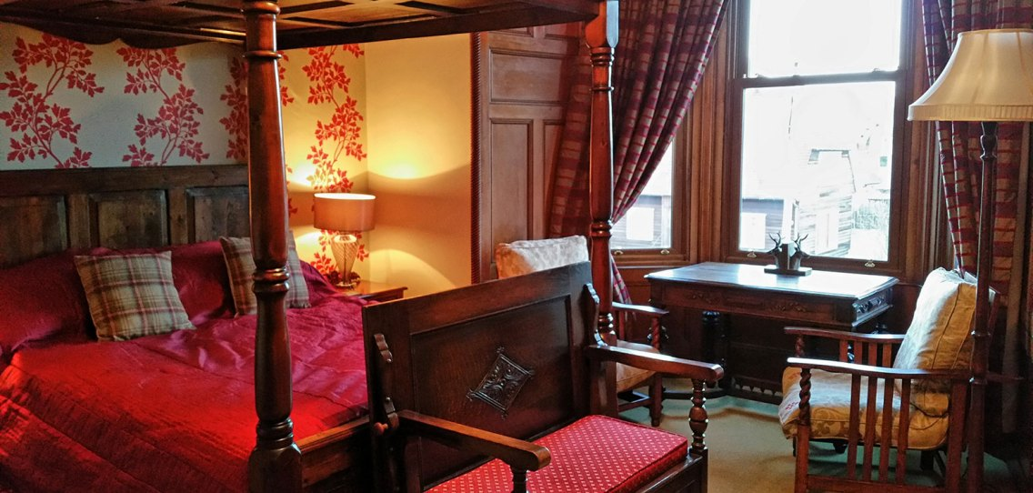 The Rowan bedroom at Strathallan B&B with a four poster bed and red patterned wallpaper