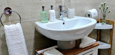 White bathroom sink unit with Scottish Fine Soap products and fluffy white towels