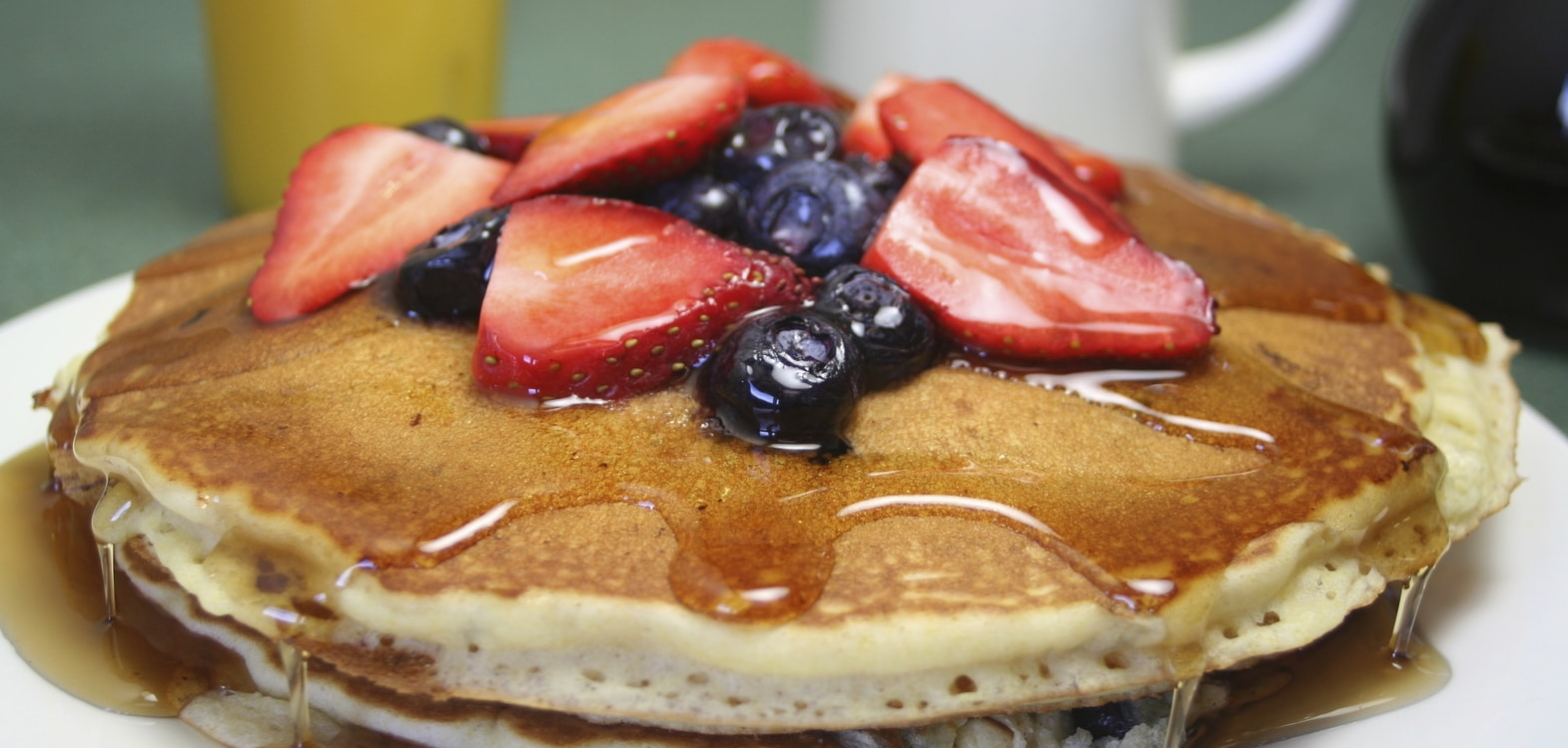 Homemade pancakes with fresh fruit on top and covered in runny honey and maple syrup