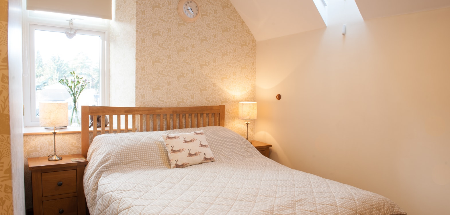 Double bed made up with pale bedding in a light and bright bedroom at Strathallan Guest House