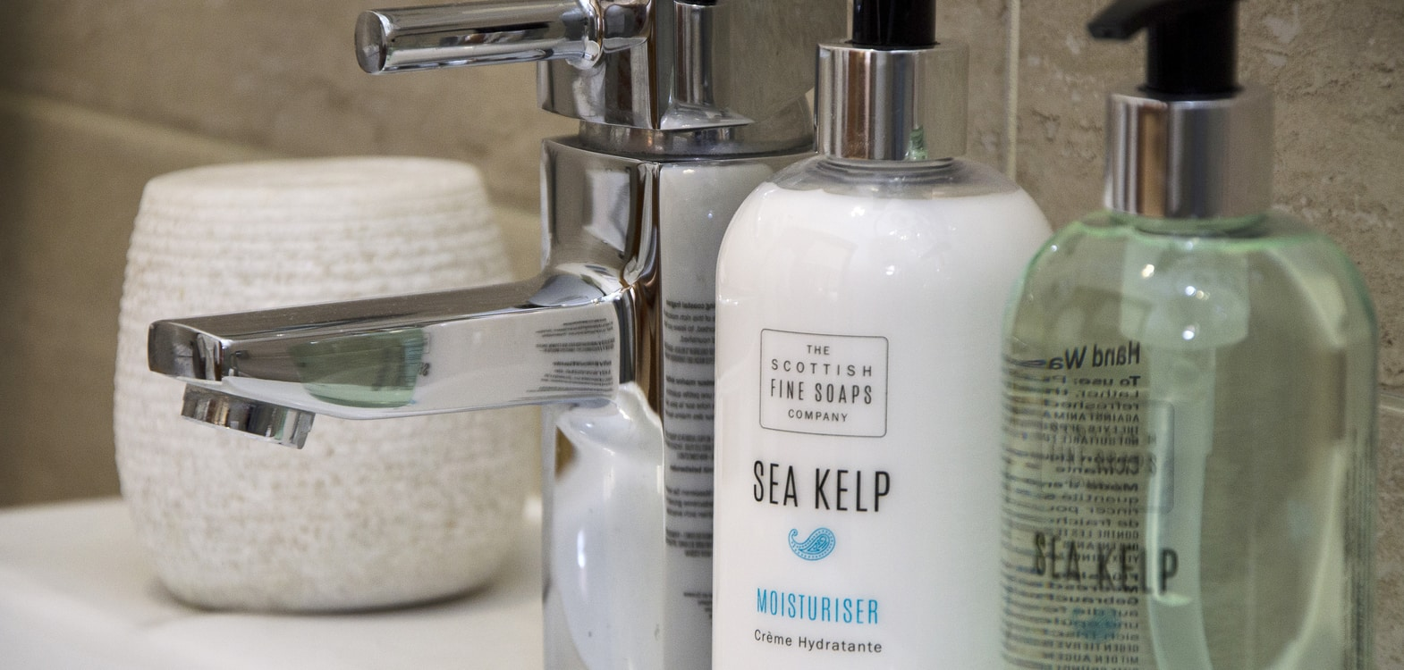 Close up of The Scottish Fine Soaps Company sea kelp handwash and moisturiser with a chrome sink tap