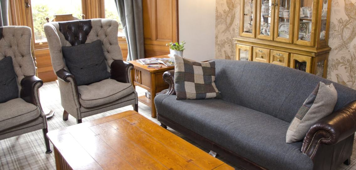 Two high backed chairs and a large sofa in the guests lounge at Strathallan Guest House