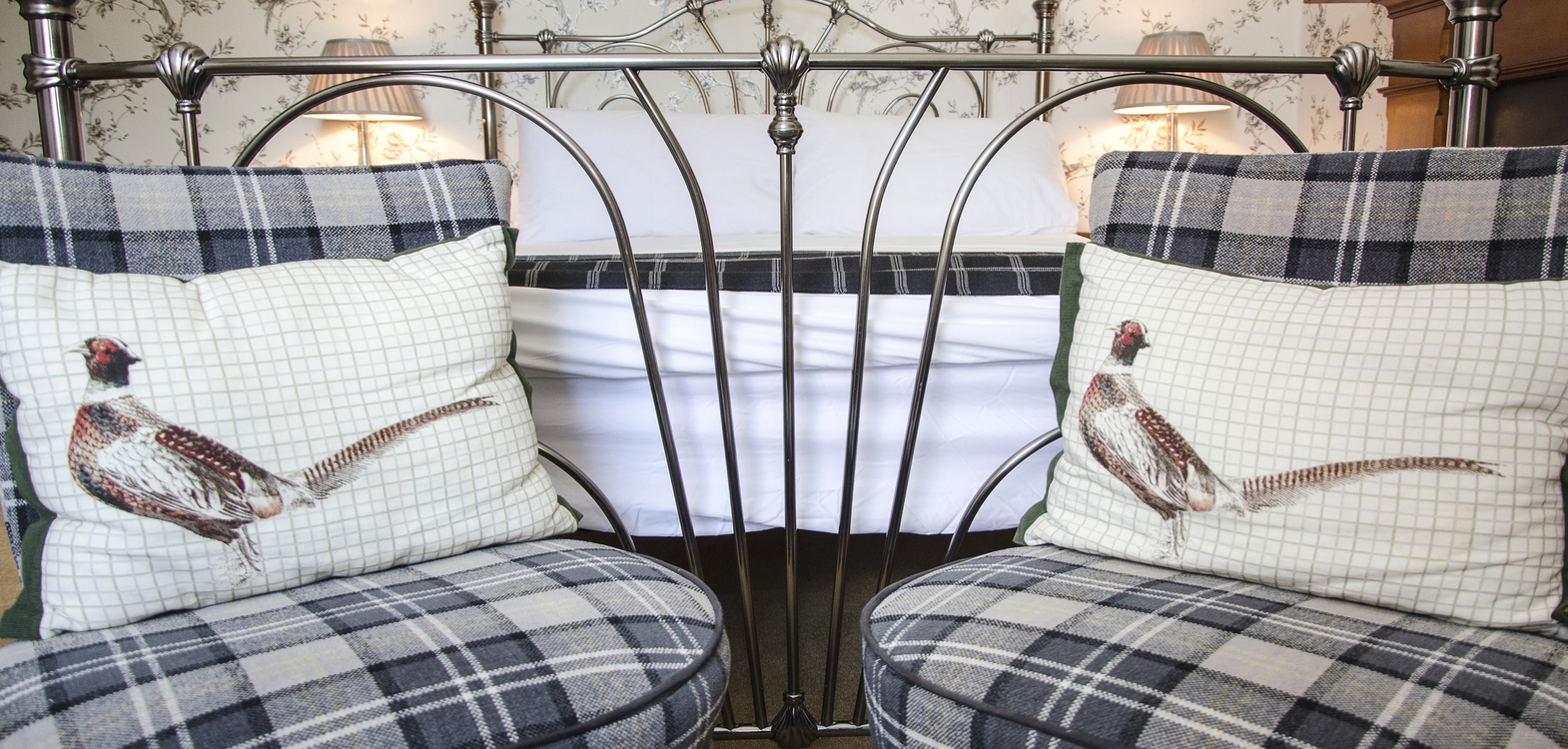 two grey tartan checked chairs at the end of a framed bed with cushions with pheasant covers