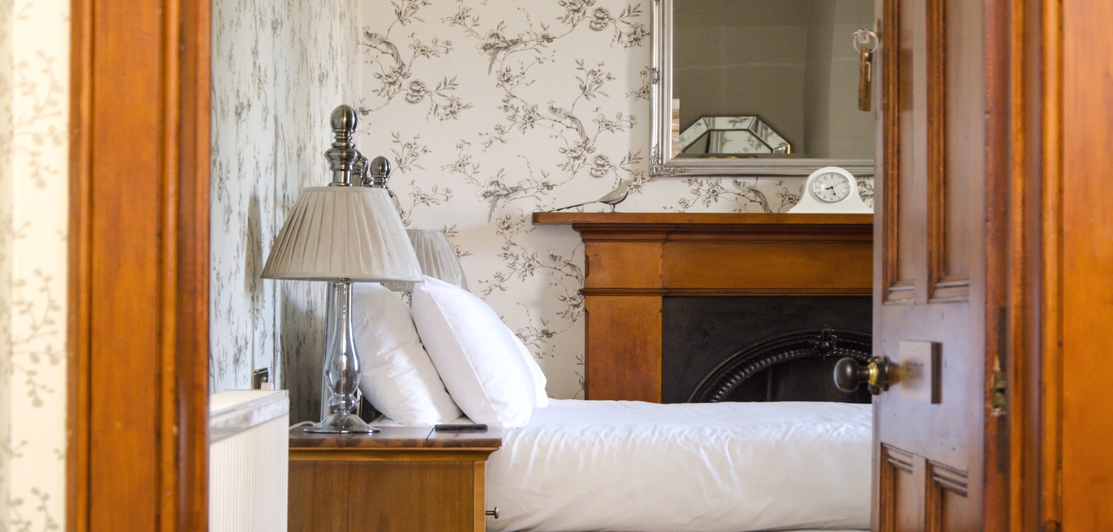 Looking into a bedroom at Strathallan Guest House showing a made up bed with white bed linen and a delicate patterned wallpaper