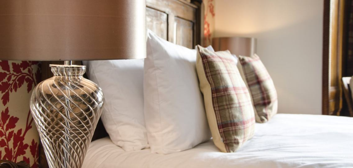 Close up of a glass lamp base with a brushed pale gold lampshade in front of a bed with white pillows and tartan cushions