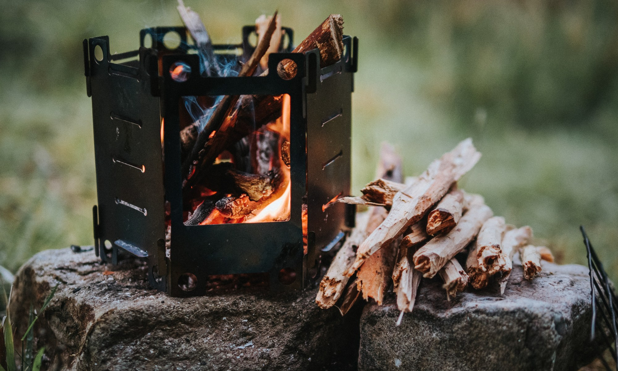 honey stove titanium, burning small branches, perched on a rock