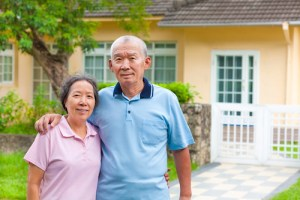 How to Use Your Home to Stay at Home happy asian senior couple standing in front of a house