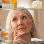 Senior woman looking through medicine cabinet