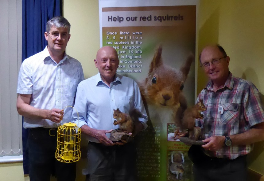 Michael Holgate (left) of Silverdale holiday park demonstrates a squirrel-proof bird feeder at the campaign meeting