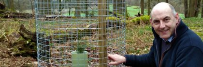 Henry Wild with one of the Scots pine saplings, meshed to prevent the park's wild deer enjoying a free snack