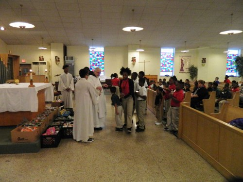 cans at the altar, and students bringing up more to donate