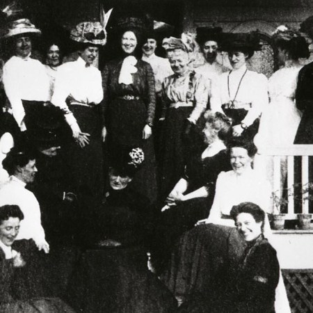 Black and white photograph of a group of ladies gathered on a porch. The women are dressed in fashions typical of the late 19th and early 20th centuries.