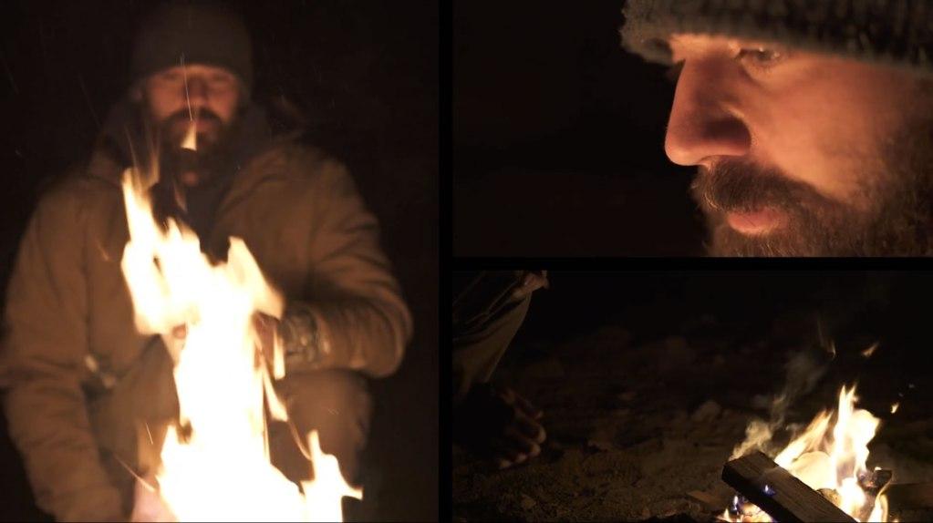 homeless man standing next to fire