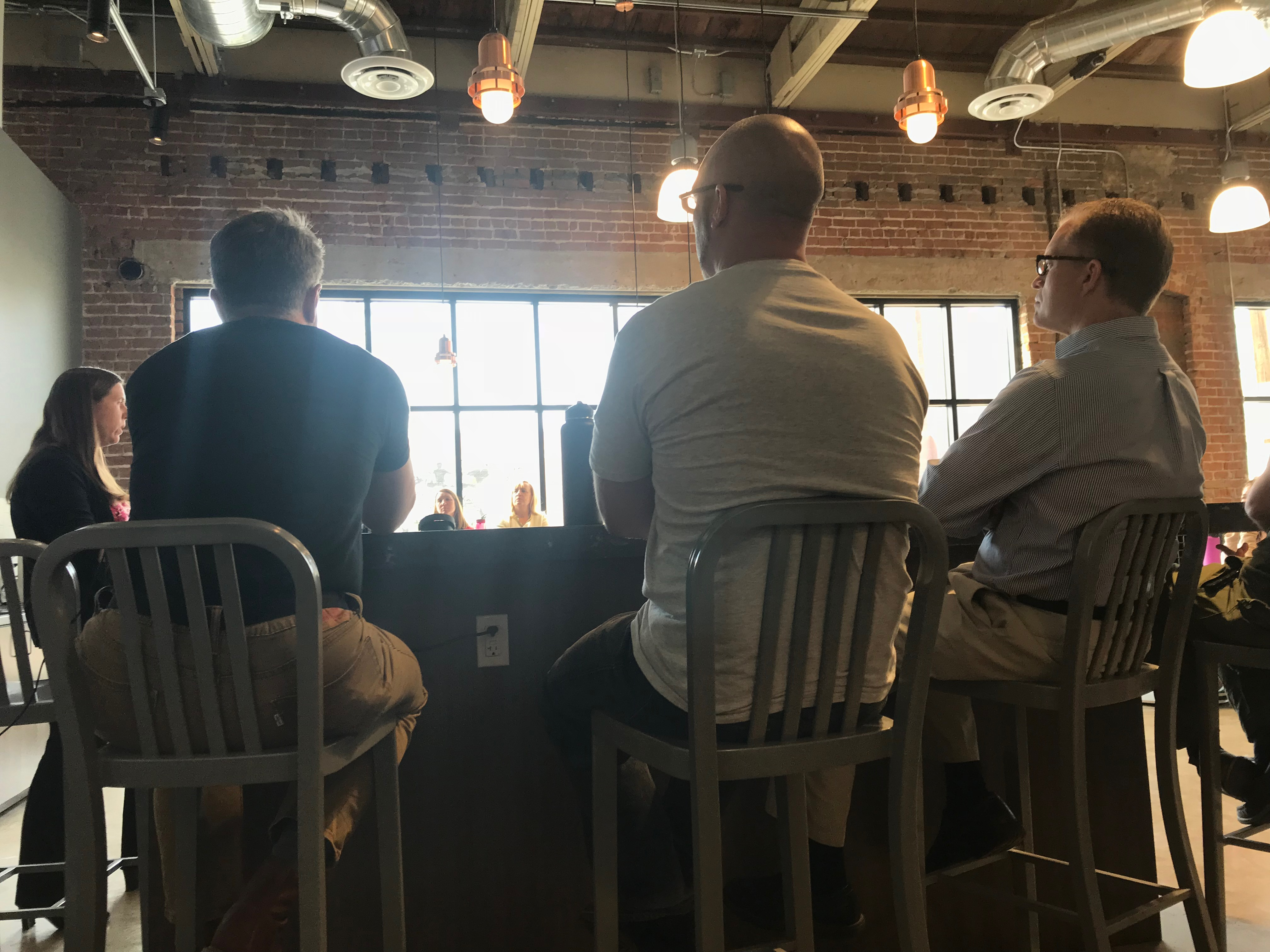 Employees sit on bar stools around the counter in the Ideas Start Here cafe at STC during a meeting.