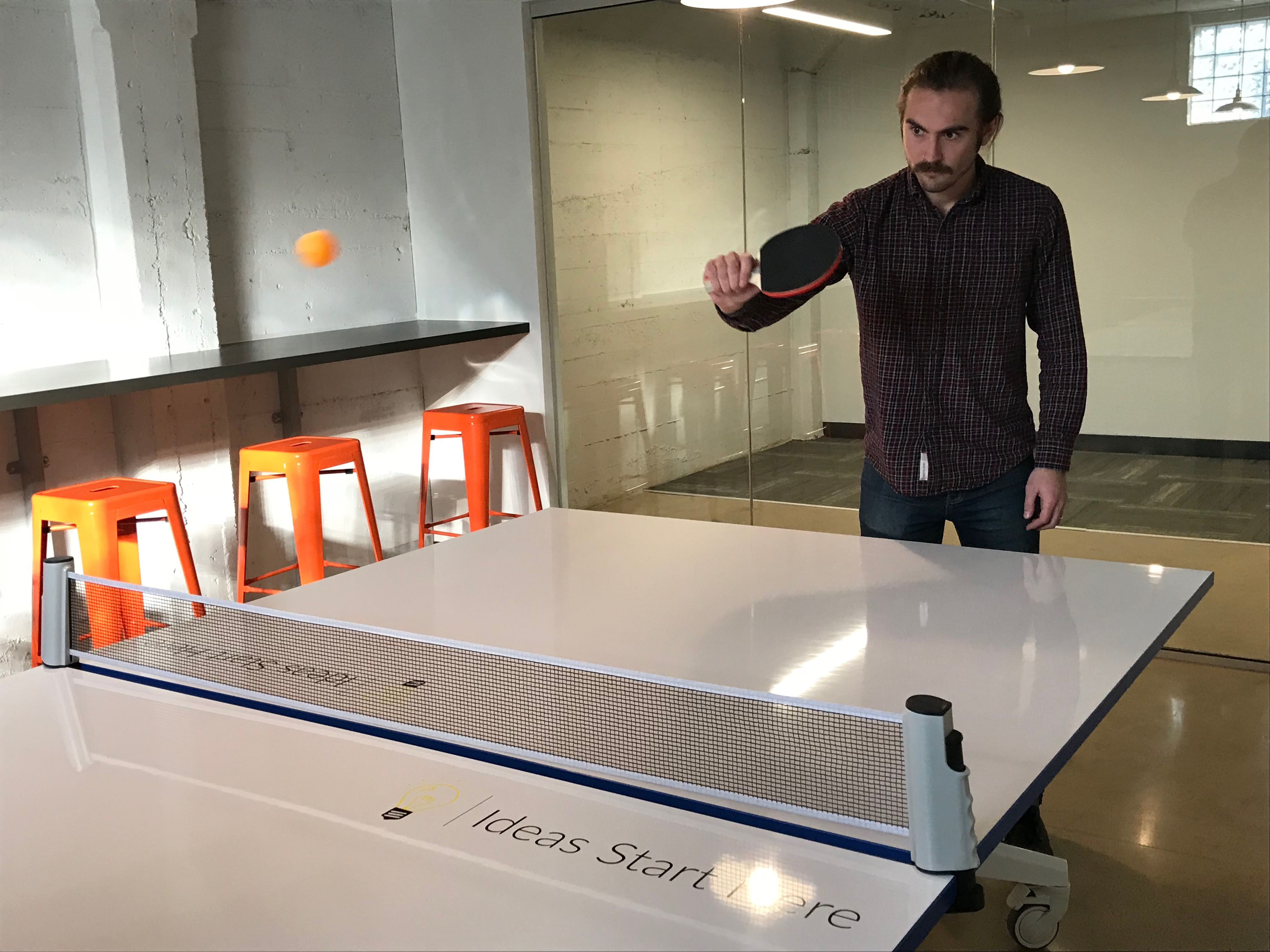 A male employee serves the ping pong ball in a room at STC's renovated warehouse in downtown Phoenix, Arizona.
