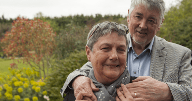 Linda Battersby with her husband Richard putting his arms around her in a beautiful garden