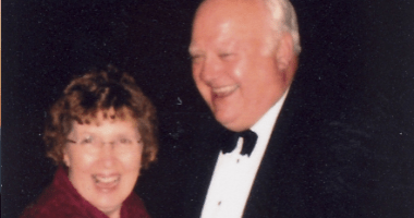 An older couple in formal wear laughing together
