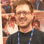 A man with a staff lanyard smiling at the camera