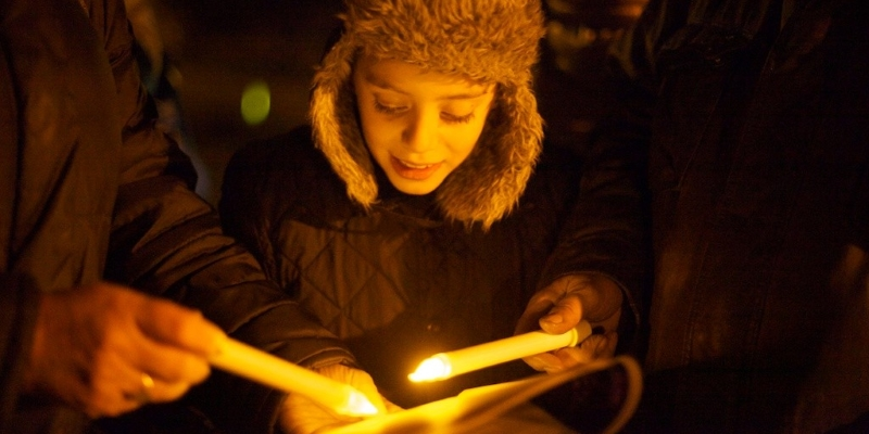 A boy reading a song book by candlelight