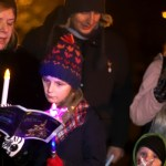 A crowd (including children) singing carols